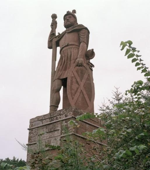 Stone figure of a bearded man wearing a kilt style outfit with cloak and helmet, carrying a sword and saltire decorated shield on top of a square plinth