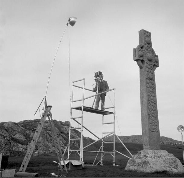Black and white photo af a large stone cross with a man standing on scaffolding taking photographs of it