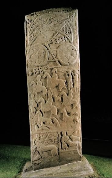 Large rectangular standing stone with Pictish motifs including crescents and circles as wll as  people riding horses and playing horns