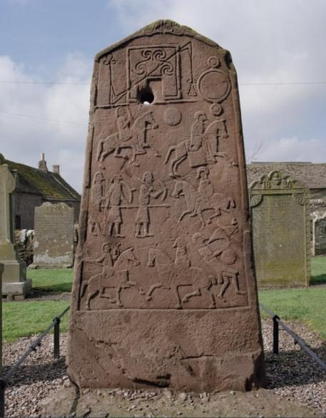 A large standing stone in a graveyard showing Pictish figures with weapons and riding horses as well as Pictish motifs