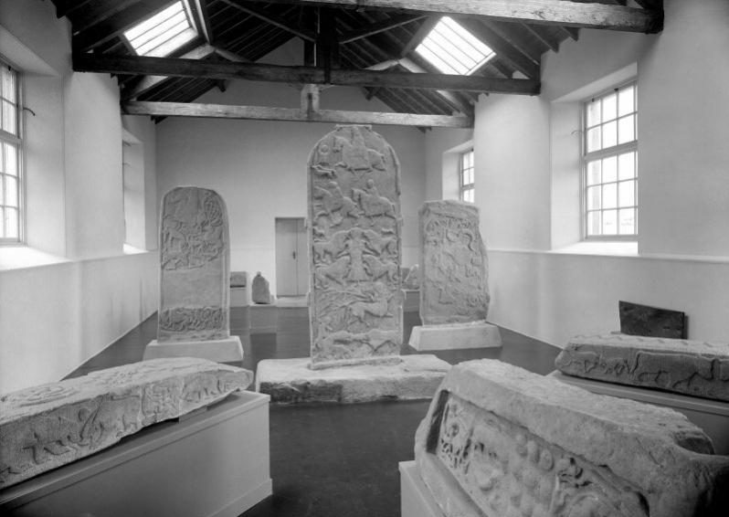 Black and white photo of a museum gallery with mounted Pictish, standing and recumbent stones