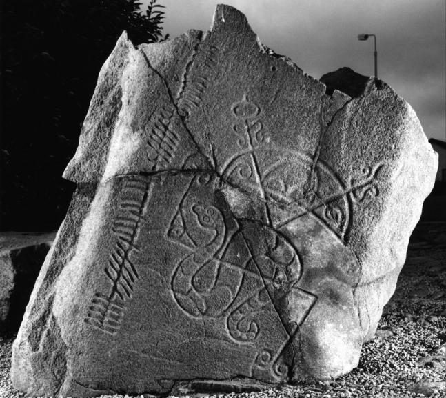 Black and white photograph of a broken stone with snake, crescent and curvilinear decoration as well as ogham script