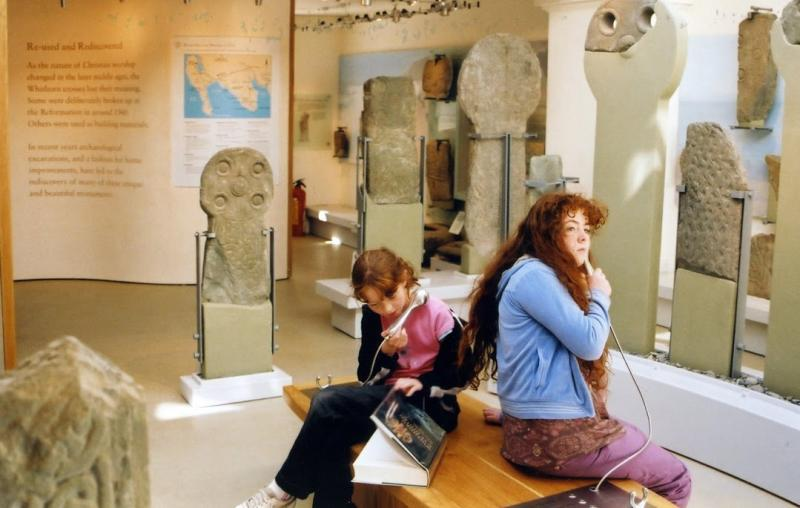 Two girls sat in a museum gallery with mounted medieval stones. One is looking at a book and both are listening to interpretation through headphones