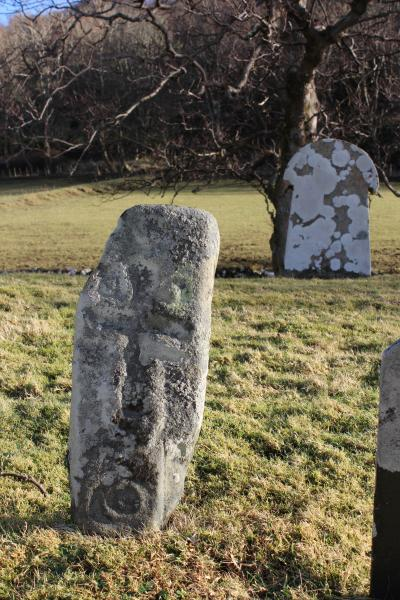 A small rectangular stone incised with a cross within a graveyard and more recent gravestones