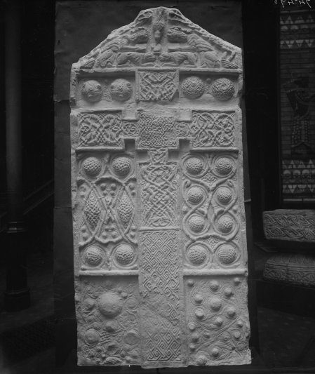 Black and white photograph of a plaster cast of a cross slab - with pointed top, bosses and circulinear decoration