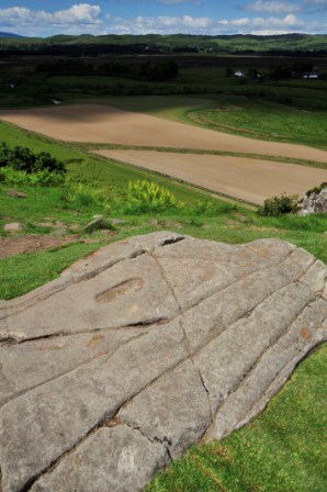A slab of what looks like stone with an incised stone footprint on top of a grassy hill with views of surrounding landscape