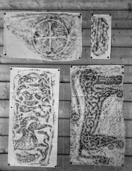 Four paper and charcoal rubbings pinned to a wooden wall