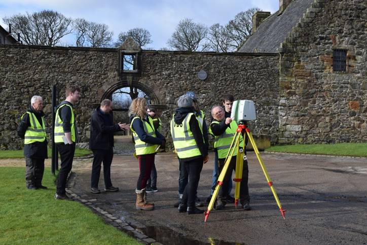 Eight people in high-vis jackets standing in a garden, with one showing the others how to use a laser scanner