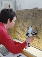 A woman holding a portable XRF machine pressed up to the surface of a stone carving