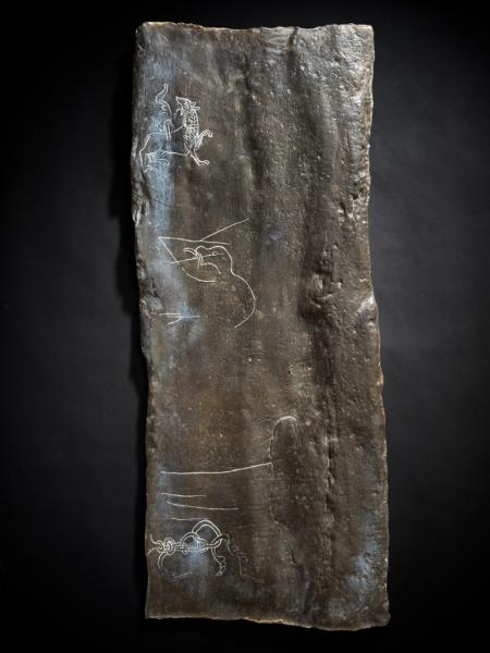 A photograph of a plaster cast painted brown showing incised animal images and lines