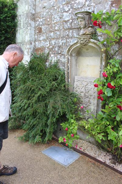 A photograph of a man looking at a carved stone fragment set in a niche of an external wall, surrounded by plants and roses