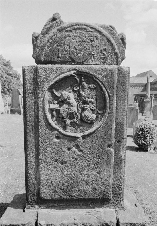 Black and white photo of a stone gravestone with heraldic symbols and emblems