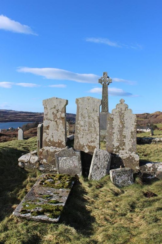 A photo of old gravestones in a graveyard, with a celtic cross in the background, and set in a rural location