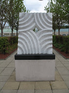 A photo of a modern stone sculpture, rectangular in shape with carved wave pattern and a diamond hole in the middle, sat on a plinth in a car park