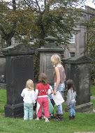 Three children and an adult, who is holding a piece of paper, looking at gravestones in a churchyard