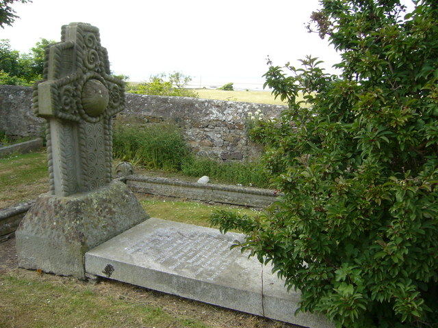 A two piece grave monument with a large rectangular flat stone with writing and a large standing cross shaped stone behind with wave and circular decoration