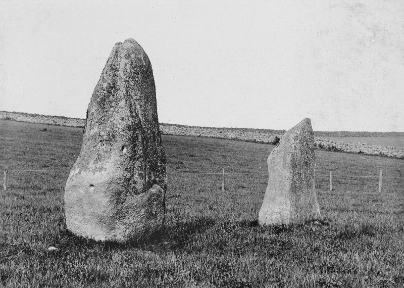 Black and white photo of two standing stones in a field - a larger on in the foreground