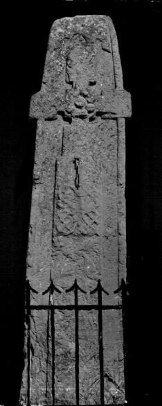 BLack and white photo of a carved cross slab with iron pointed top railings in front