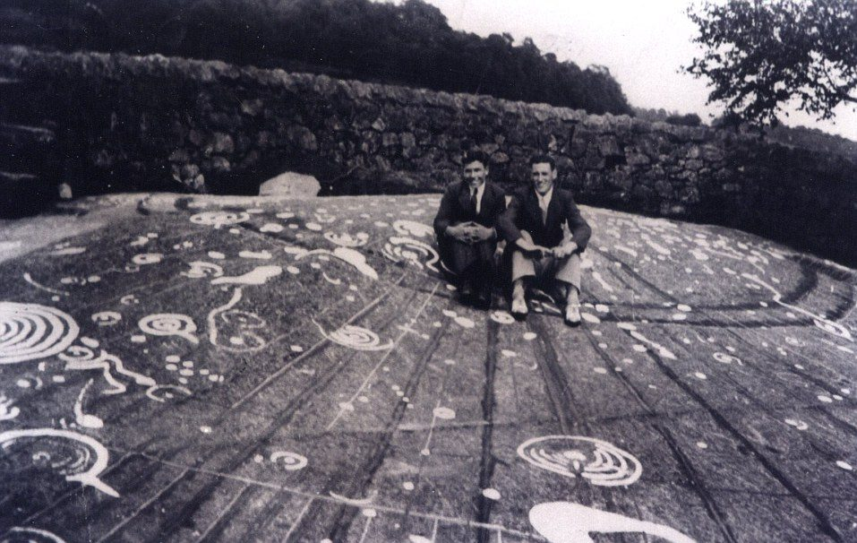 A black and white photo of two young men sitting on a large flat stone. Cup and ring marks and other motifs have been highlighted on the stone using paint.