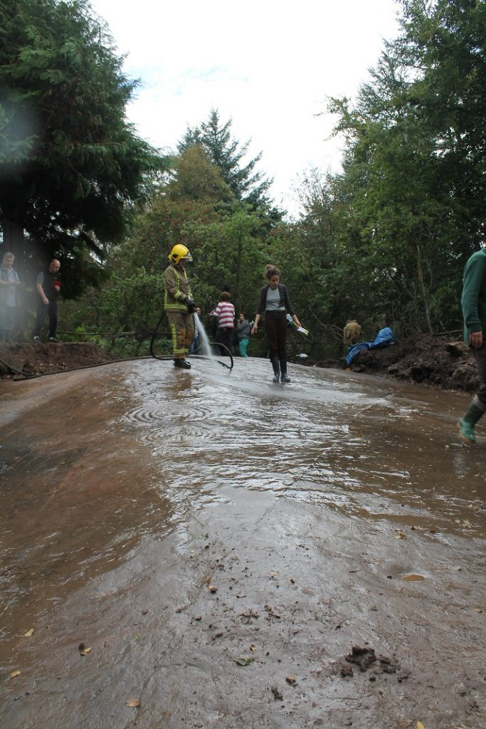 A photo of a fireman with a hose, washing the surface of a large flat stone surface with other people helping to clean it