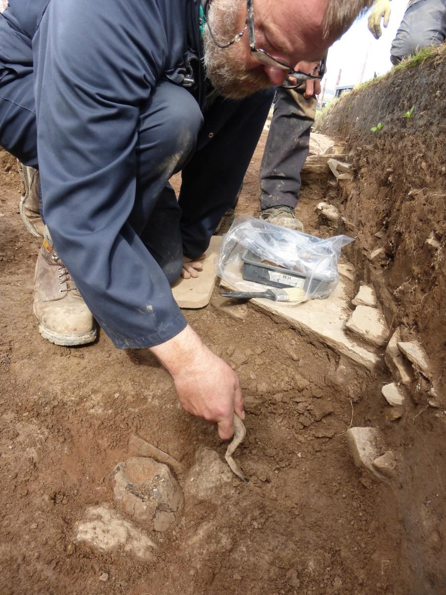 A photograph showing a man in a trench excavating pottery sherds with a trowel