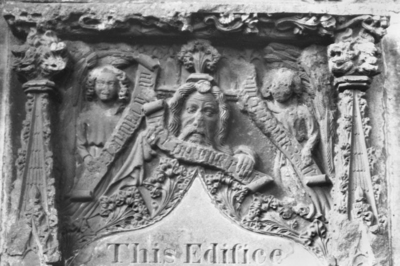 Close up black and white photo of a detail of a stone ediface with a male head, two angels and pinnacles