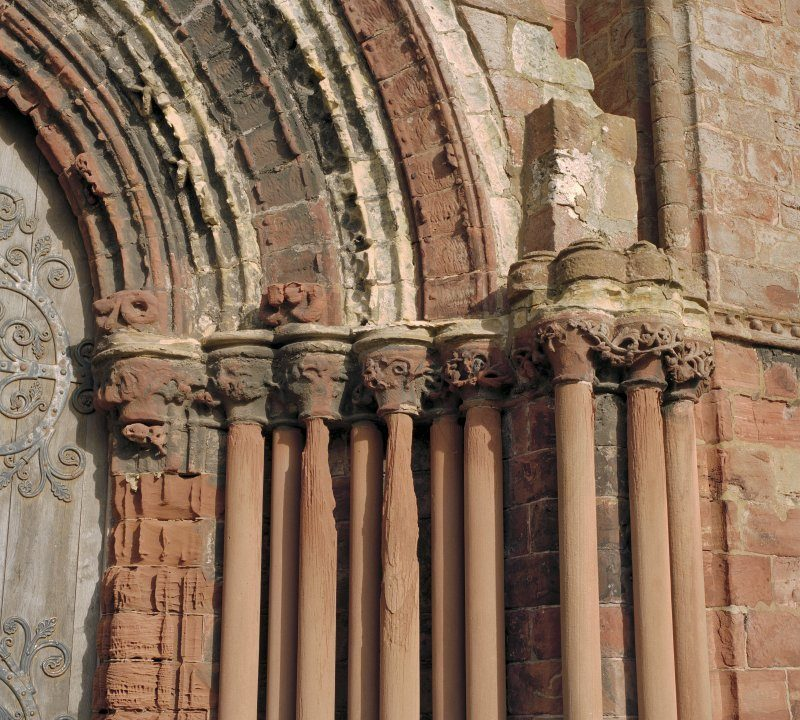 Close up colour photo of the pinnacles of stone columns in red sandstone which are heavily worn, around a doorway