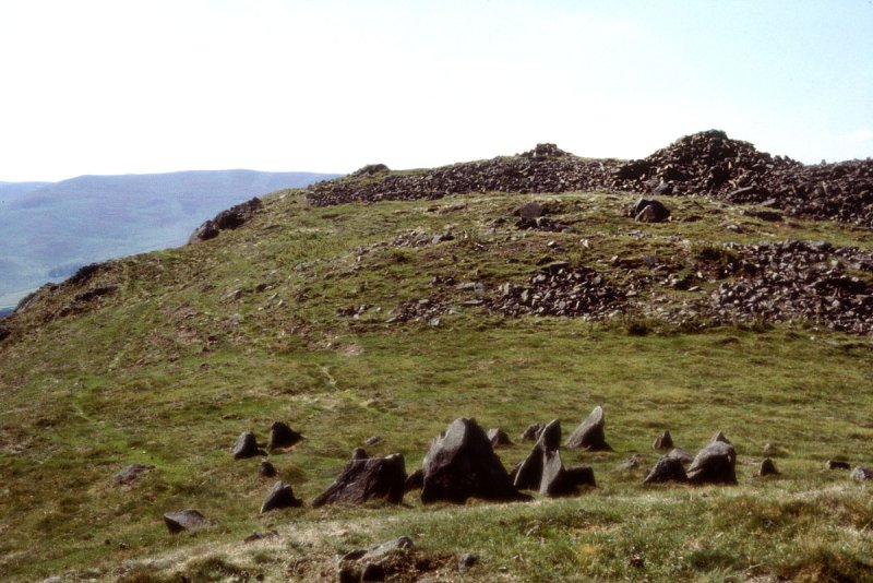 A photograph of a grassy summit showing large protruding pointed boulders and the remains of a hill fort surrounded by the spread of a degraded substantial wall in the background