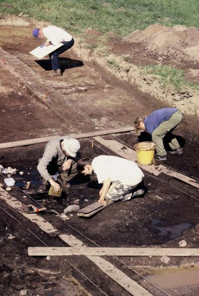 A photograph of an archaeological excavation showing people with buckets and sponges excavating in a boggy area and a person in the background plan drawing