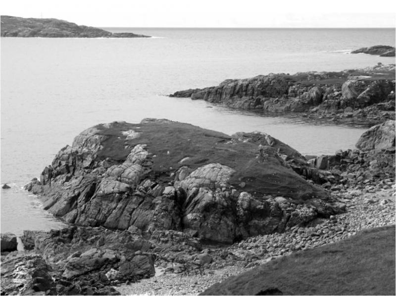 A black and white photograph of a rocky shoreline with a point of high land jutting out into the sea