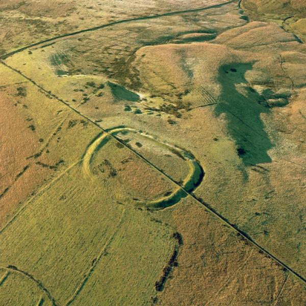 An oblique aerial photograph showing a large penannular earthwork in an upland location