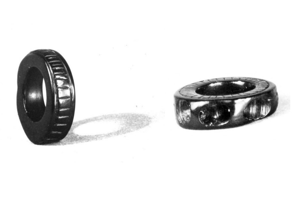 A photograph showing two chunky jet rings, one decorated with lines along the edge, and another decorated with oval indentations along the edge and radial lines on the side