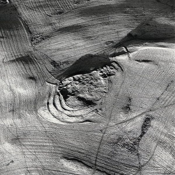 A dramatic black and white oblique aerial photograph showing extensive remains and earthworks surrounded by an expanse of fields and rig and furrow