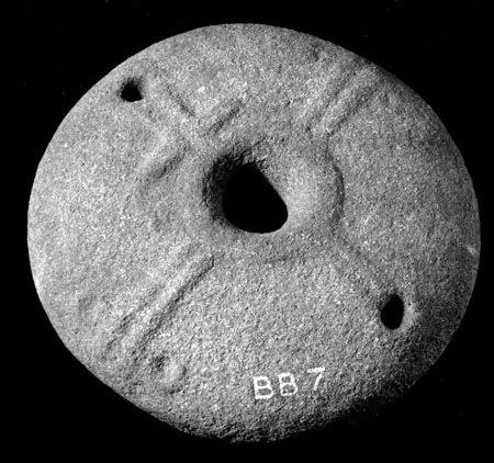 A black and white photograph of a circular stone decorated with a cross in relief with a large central perforation and a smaller