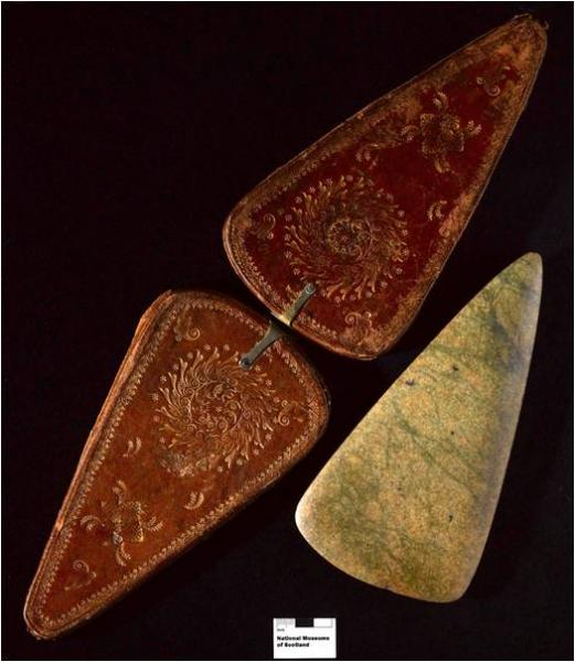 A photograph showing a triangular marbled green axehead and a modern reproduction of a decorated leather carrying case