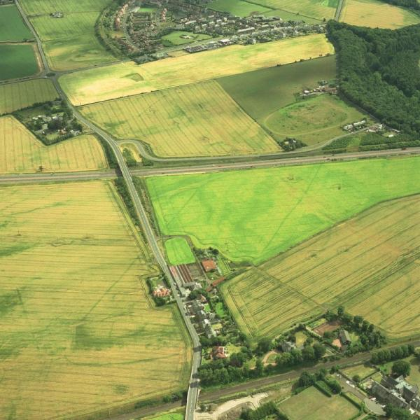 An aerial photograph showing the cropmarks of two parallel lines in a landscape of agricultural fields, roads and settlement