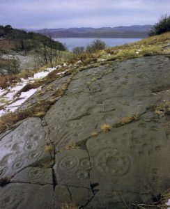 A photograph of a large area of bedrock carved with cupmarks and cup and ring motifs in an elevated position with trees, water and hills in the background
