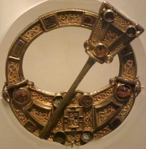 A photograph of an ornate large pennanular brooch decorated with silver and gold filigree and amber stones