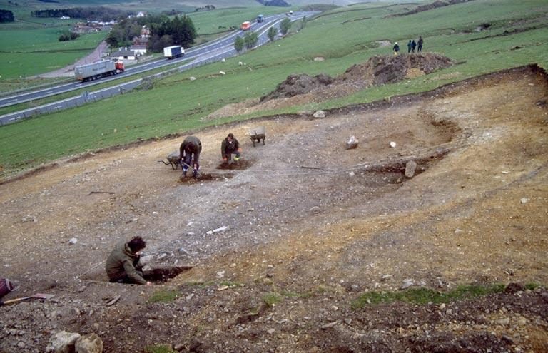 A photograph showing people excavating deposits of a circular platform on a sloping landscape with fields and a road in the background