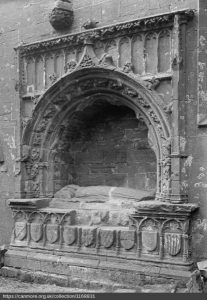 Black and white photograph of a canopied tomb with effigy of Margaret lying on a slab, within a wall