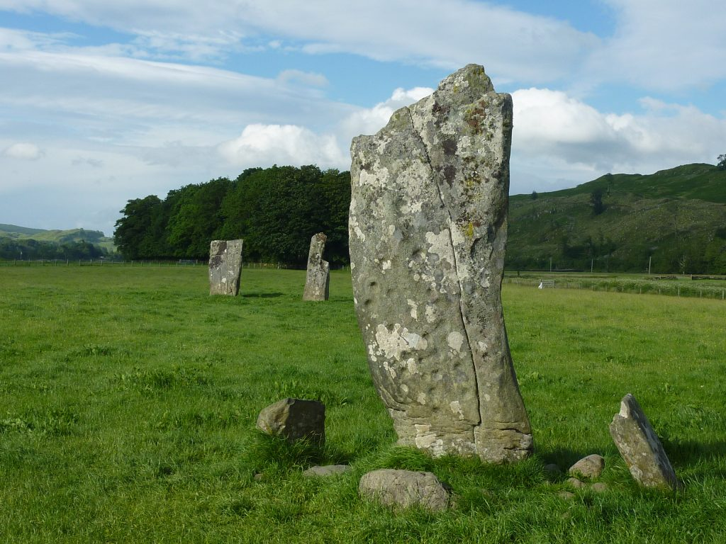 A photograph of a standing stone with cup and ring carvings standing in a wider landscape of standing stones
