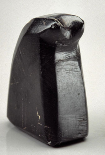 A photograph of a small upright and curved piece of polished jet